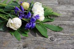 Blumenstrauß auf einem Holz, Pfingstrosen und Iris Stockfotos