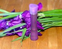 Blumenstrauß der Blenden und der kosmetischen Flasche Stockbild
