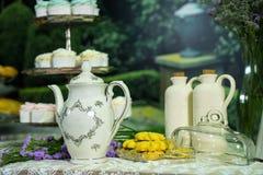 Blumenstrauß der Blume, des Krugs tae und der Plätzchen in einer Glasplatte auf dem Tisch mit Hintergrund des kleinen Kuchens Stockfoto