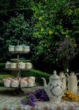 Blumenstrauß der Blume, des Krugs Tees und der Plätzchen in einer Glasplatte auf dem Tisch Stockfotografie