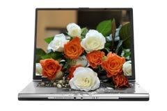 Blumenstrauß der Blumen auf Laptop Lizenzfreies Stockfoto
