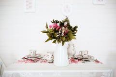 Blumenstrauß der Blumen auf Tabelle Weißer Hintergrund Abbildung der roten Lilie Lizenzfreie Stockfotos