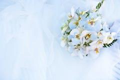 Blumenstrauß der Blumen und des Hochzeitskleides Stockbild
