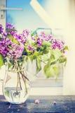 Blumenstrauß der Flieder in einem Glaskrug auf dem Tisch über Fensterhintergrund Lizenzfreie Stockfotografie