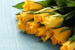 Blumenstrauß der gelben Rosen auf blauem Hintergrund Stockbild