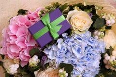 Blumenstrauß der Hortensie und der Rosen mit einem Geschenk Stockfotografie