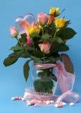 Blumenstrauß der mehrfarbigen Rosen in einem Vase mit rosafarbenem Farbband Lizenzfreie Stockfotos