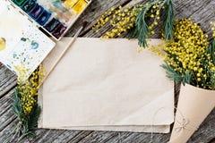 Blumenstrauß der Mimose Verbände twine und Scheren auf rustikalem Holztisch, altem Papier für Text und Aquarellen Lizenzfreie Stockfotografie