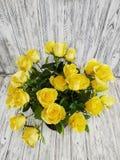 Blumenstrauß der Nahaufnahme der gelben Rosen auf hölzernem Weinlesehintergrund stockbild