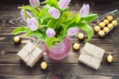 Blumenstrauß der purpurroten Tulpe im rosa Vase mit Geschenkboxen und kann Stockfoto