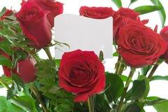 Blumenstrauß der recht roten Rosen mit einer unbelegten Karte. Lizenzfreies Stockfoto