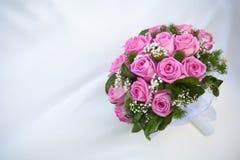Blumenstrauß der rosafarbenen Rosen auf dem weißen Hochzeitskleid Lizenzfreie Stockfotografie