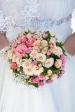 Blumenstrauß der rosafarbenen Rosen in den Händen der Braut Lizenzfreies Stockfoto