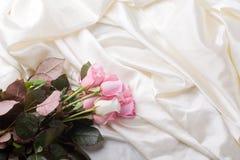Blumenstrauß der rosafarbenen und weißen Rosen, die in Seide legen Lizenzfreies Stockbild