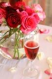 Blumenstrauß der Rosen und des Glases Champagners Stockbild