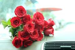 Blumenstrauß der roten Rosen auf Autokonsole Lizenzfreies Stockfoto