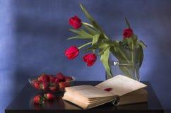 Blumenstrauß der Tulpen, der Erdbeere und des Buches Stockfotos