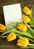 Blumenstrauß der Tulpen mit unbelegter Karte auf altem hölzernem lizenzfreies stockfoto