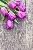 Blumenstrauß der violetten Tulpen auf der Eichenbrauntabelle Lizenzfreie Stockfotos