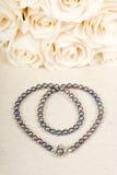 Blumenstrauß der weißen Rosen und der schwarzen Perlen-Halskette stockfotografie