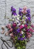 Blumenstrauß der wilden Blumen auf grauem Leinenhintergrund, Draufsicht Lizenzfreie Stockbilder
