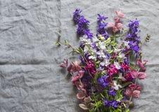 Blumenstrauß der wilden Blumen auf grauem Leinenhintergrund, Draufsicht Abbildung der roten Lilie Freier Raum Lizenzfreies Stockfoto