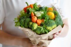 Blumenstrauß des Brokkolis, des Selleries, der Karotten, des Paprikas und des Kopfsalates in den Händen einer Frau Stockfotografie