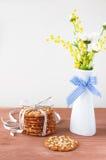 Blumenstrauß des Frühlinges blüht auf dem Tisch und Plätzchen Stockbild