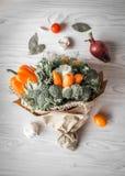 Blumenstrauß des Frischgemüses liegt auf einem weißen Holztisch Ist in der Nähe eine rote Zwiebel, Tomaten, Knoblauch, Lorbeerbla Stockbild
