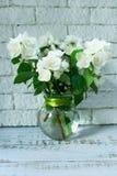 Blumenstrauß des Jasmins in einem transparenten Vase auf einem weißen Backsteinmauerhintergrund stockfoto