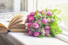 Blumenstrauß des Klees und des alten Buches auf dem Fenster Stockfotos