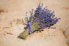 Blumenstrauß des Lavendels gebunden mit dem Band, das auf dem Sand liegt Stockbilder