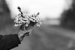 Blumenstrauß des Schneeglöckchens in der Hand verlängerte vorwärts, auf der Seite der Straße Lizenzfreies Stockfoto