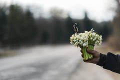 Blumenstrauß des Schneeglöckchens in der Hand verlängerte vorwärts, auf der Seite der Straße Stockfotografie