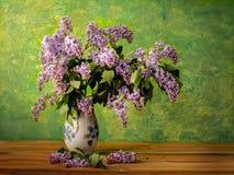 Blumenstrauß Frühling purpurroter Flieder in einem Vase auf einem gemalten Hintergrund Lizenzfreie Stockfotos