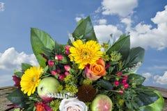 Blumenstrauß mit Herbstdekorationsholztisch und blauem Himmel Lizenzfreies Stockbild