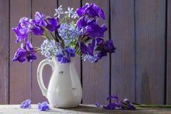 Blumenstrauß mit Iris auf Holztisch Stockfotografie