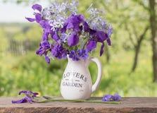 Blumenstrauß mit Iris auf Holztisch Stockfotos