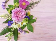 Blumenstrauß-Rahmendesign der Rosen schönes festlich auf einem rosa hölzernen Hintergrundjasmin, Magnolie stockbild