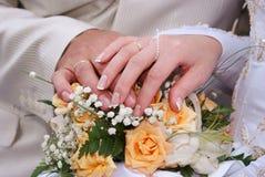Blumenstrauß und Hände mit Ringen Lizenzfreies Stockfoto
