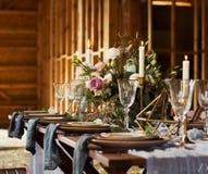 Blumenstrauß und Kerzen Hochzeitsfest Viele Weingläser auf grüner Tabelle Abbildung der roten Lilie Stockbild