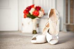 Blumenstrauß und Schuhe vor Kirche Lizenzfreies Stockbild