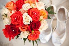 Blumenstrauß und Schuhe vor Kirche Stockfotografie