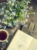 Blumenstrauß von blauen Blumen des Sommers, von Tasse Tee und von Weinlesebüchern Lizenzfreies Stockfoto