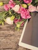 Blumenstrauß von Blumen auf einem Holztisch mit einem Tablet-Computer-Esprit stockfoto