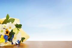 Blumenstrauß von Blumen auf einer Holzoberfläche gegen blauen Himmel Stockbilder