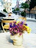 Blumenstrauß von Blumen auf einer Tabelle Kaffee im im Freien Lizenzfreies Stockfoto
