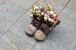 Blumenstrauß von Blumen in den geflochten Stiefeln Stockbild