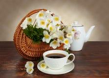 Blumenstrauß von Blumen in einem Korb und ein Becher Tee Stockfoto