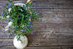Blumenstrauß von Blumen im Tee-Topf auf hölzernen Planken stockfotografie